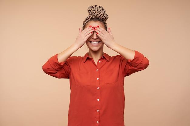 Piacevole giovane signora bruna allegra con la fascia che copre gli occhi con i palmi sollevati e sorride ampiamente, in piedi contro il muro beige Foto Gratuite