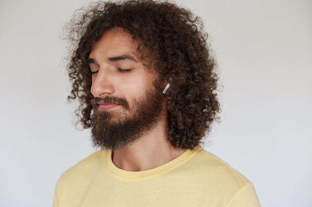 Приятный молодой темноволосый кудрявый мужчина с пышной бородой в наушниках в желтой футболке, слушает музыку и держит глаза закрытыми Бесплатные Фотографии