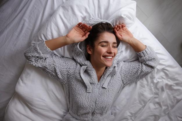 Приятно выглядящая молодая темноволосая симпатичная женщина, лежащая в постели в повседневной серой одежде, искренне улыбаясь с поднятыми руками и с закрытыми глазами, изолирована от домашнего интерьера Бесплатные Фотографии