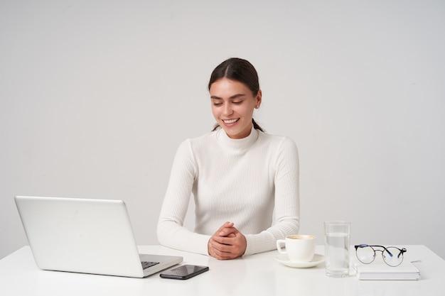 Piacevole giovane bella signora dai capelli scuri con trucco naturale che piega le mani mentre è seduto a tavola sul muro bianco e sorride positivamente, vestito con abiti formali Foto Gratuite
