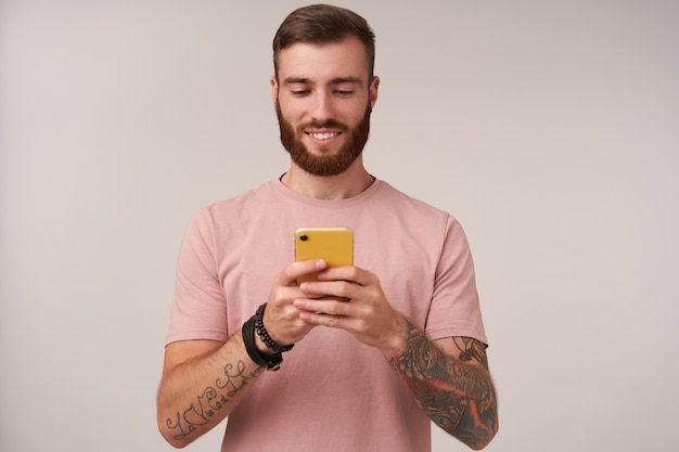 Pleasant looking young tattooed brunette male with short haircut holding smartphone in raised hands and chatting with his friends, standing on white with sincere smile Free Photo