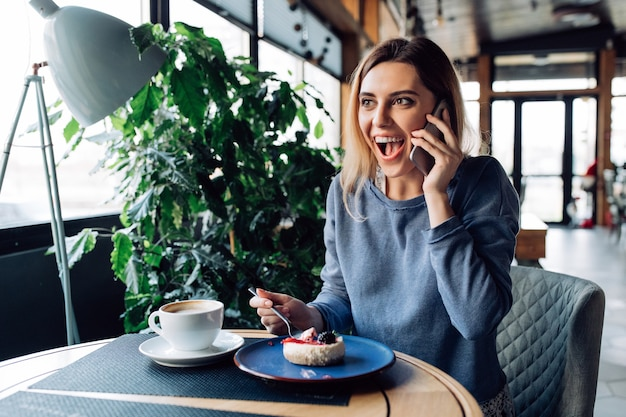 Pleasantly surprised girl having phone conversation, eating dessert and drinking coffee Free Photo