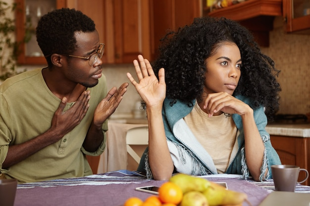 Please forgive me. unhappy african american male cheater holding hand on his chest apologizing to beautiful indifferent woman who ignoring and refusing all his excuses, telling him to get lost Free Photo