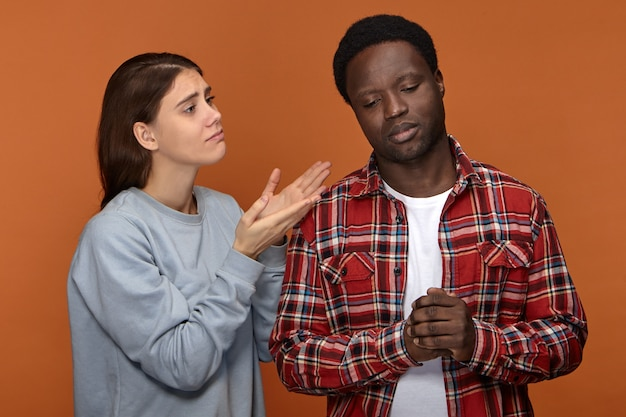 Please forgive me. unhappy worried young caucasian woman gesturing having mournful facial expression, asking her offended upset dark skinned husband for forgivenes. people and relationships Free Photo