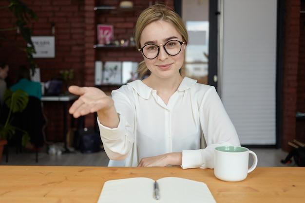 Пожалуйста, присядь. крытый снимок красивой дружелюбной молодой кавказской бизнес-леди в очках, улыбающейся и приветствующей жест во время деловой встречи с партнером или клиентом в кафе Бесплатные Фотографии