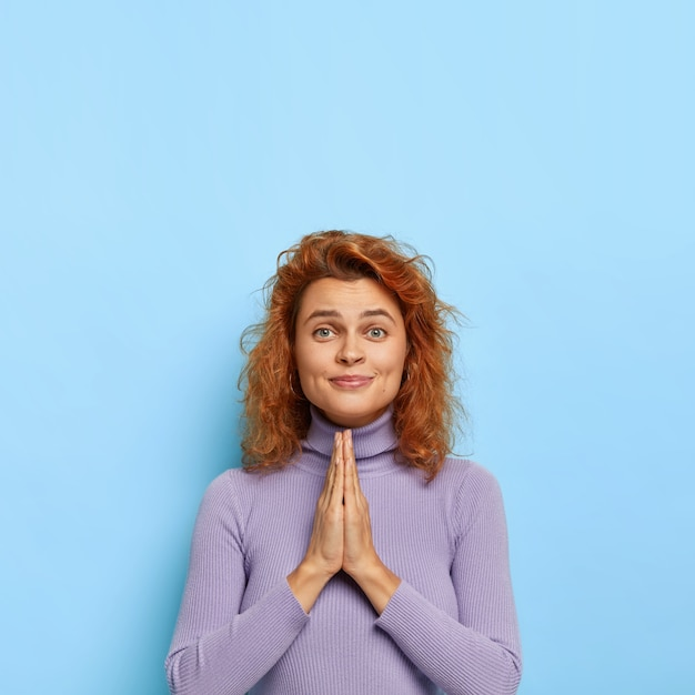 Please, help me one more time! friendly looking ginger woman keeps palms pressed together, asks for something, hopes in better, wears purple casual jumper, smiles pleasantly , copy space up Free Photo