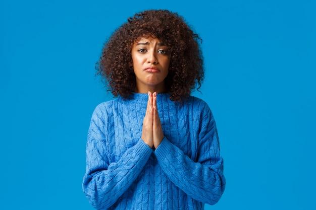 Пожалуйста, помогите мне. дуться мрачная милая афро-американская подруга с афро-стрижкой, пожать друг другу руки в молитве, молиться, просить прощения, извинить за ошибку, просить над синей стеной Premium Фотографии