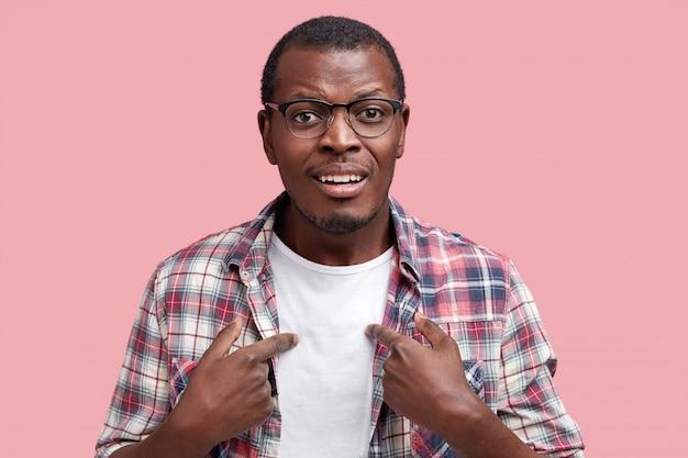 アフリカ系アメリカ人の若い男が白いtシャツと市松模様のシャツを着て満足している 無料写真