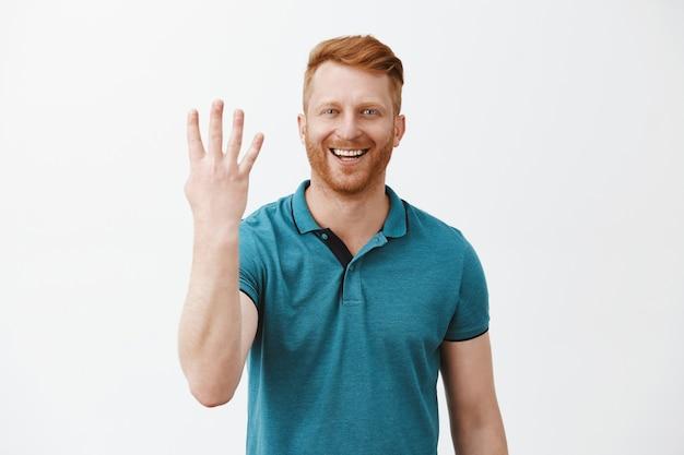 Довольный и довольный мужчина-рыжий клиент с щетиной в зеленой рубашке-поло показывает номер четыре пальцами и широко улыбается Бесплатные Фотографии
