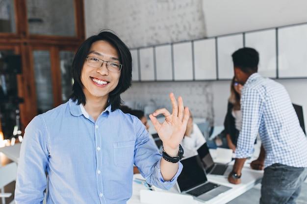 동료와 회의 후 괜찮아 기호로 포즈 클래식 파란색 티셔츠에 기쁘게 아시아 남자. 좋은 하루를 즐기는 안경에 행복 한 중국 기업가의 실내 초상화. 무료 사진