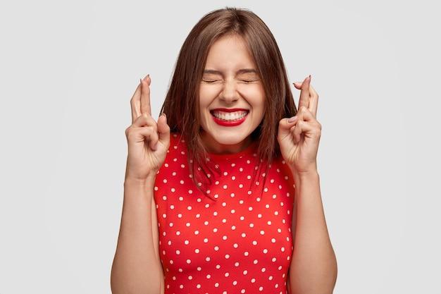 기뻐하는 매력적인 유럽 여성이 이기고 싶어하고, 교차 손가락으로 손을 들고, 복권 결과를 기다리고, 눈을 감습니다. 무료 사진