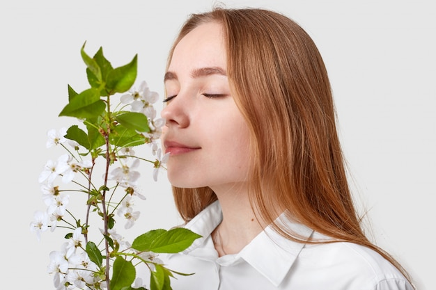 Pleased attractive woman smells cherry blossom Free Photo