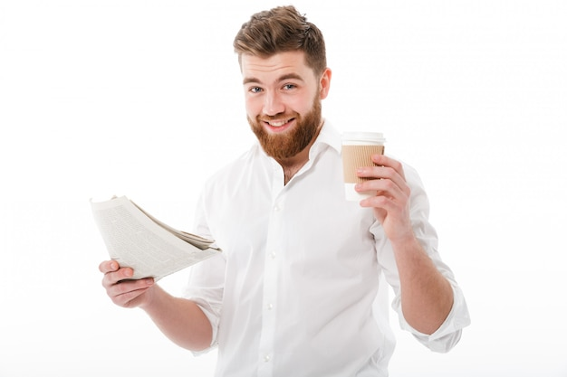 Pleased bearded man in business clothes holding newspaper Free Photo