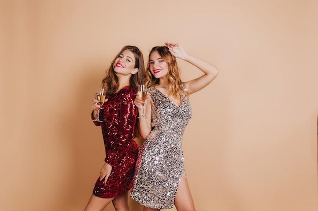 Lieta donna bionda con labbra rosse in posa con un amico alla festa di capodanno e ridendo sulla parete chiara Foto Gratuite