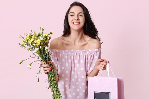 기쁘게 갈색 머리 유럽 여자 선물 가방과 꽃, 폴카 도트 드레스를 입고, 여성의 날에 선물을받을 행복, 맨 손으로 어깨를 보여 긍정적 인 모습, 실내 포즈를 보유하고 있습니다. 무료 사진