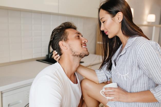 コーヒーを飲み、夫の髪をなでるパジャマで幸せなブルネットの女性 無料写真