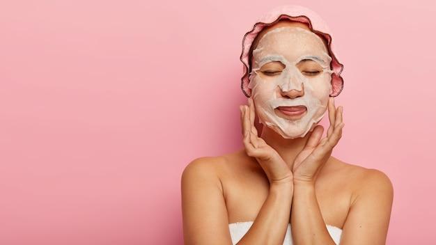 満足している中国人女性は化粧品の手順を楽しんで、頬に天然紙のフェイスマスクを持ち、タオルで包み、バスキャップを着用し、目を閉じ、ピンクの壁に隔離され、広告のための空きスペースがあります 無料写真
