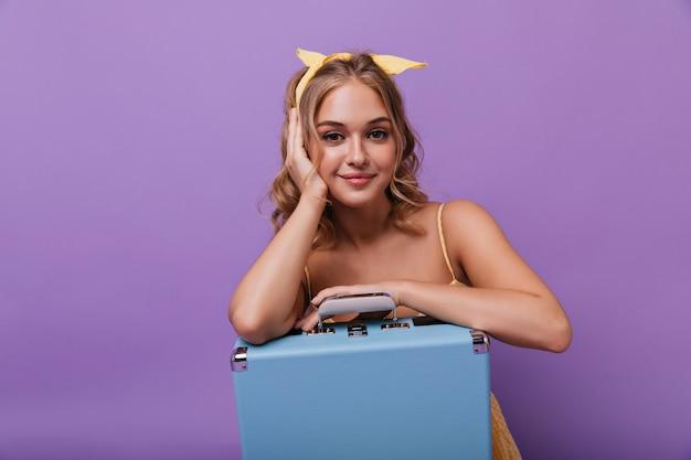 青いスーツケースでポーズをとって喜んでいる暗い目の女の子。やさしく笑顔でバイオレットに座っている熱狂的なかわいい女性。 無料写真