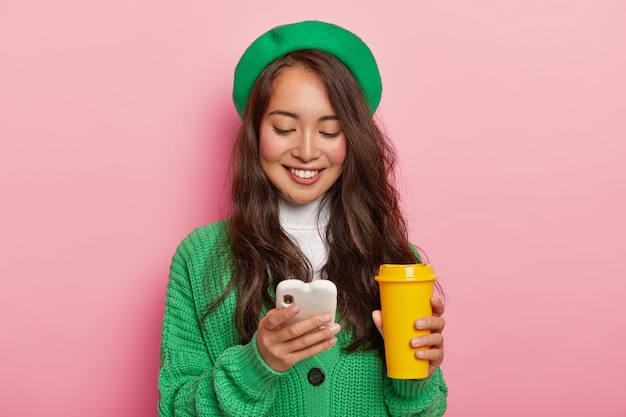 Pleased dark haired girl focused in cell phone, glad to get message of invitation for party, surfes social networks on modern gadget, checks newsfeed, wears green fashionable clothes, drinks coffee Free Photo