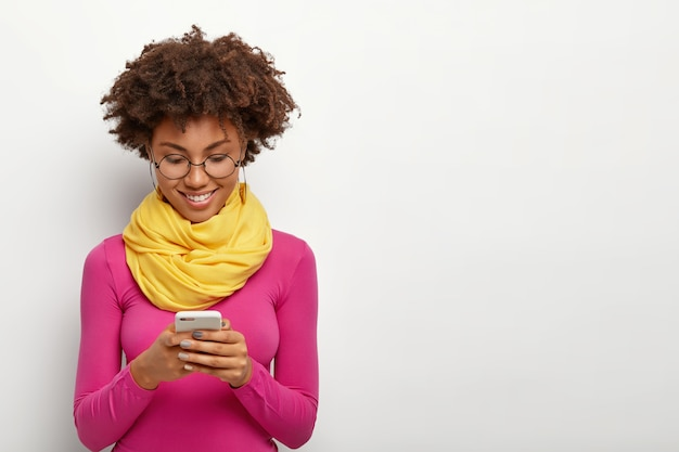 Pleased dark skinned female holds modern mobile phone, focused into display, wears pink turtleneck Free Photo