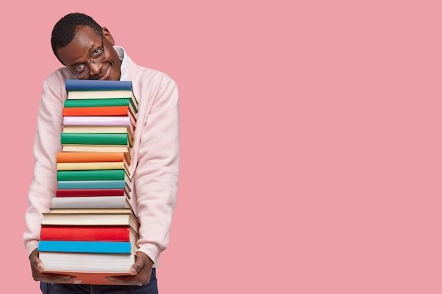 기뻐하는 어두운 피부의 힙 스터 학생이 무거운 책 더미에 기대어 캐주얼 스웨터를 입습니다. 무료 사진