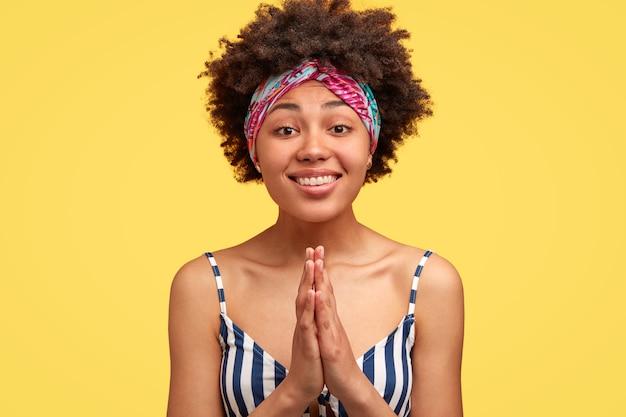 Довольная темнокожая женщина с умоляющим выражением лица, держит руки в молитвенном жесте, позитивно улыбается, носит повседневную одежду Бесплатные Фотографии