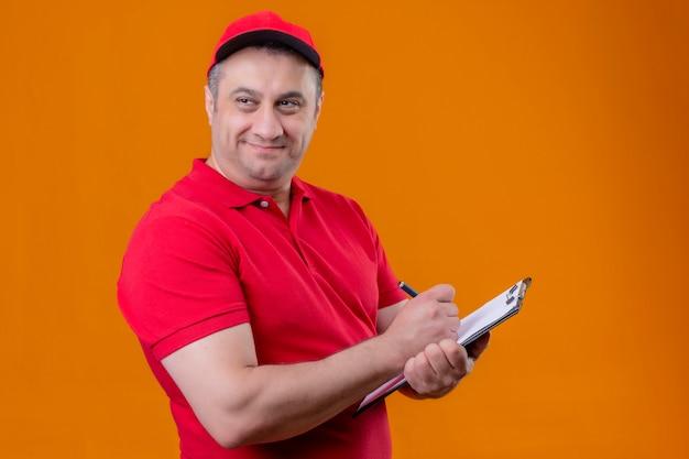赤い制服を着て満足している配達人とオレンジ色の背景の上に立って顔に笑顔でよそ見何かを書くクリップボードを保持しているキャップ 無料写真
