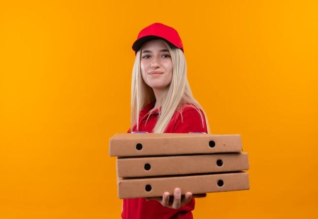 孤立したオレンジ色の背景に赤いtシャツとピザボックスを保持しているキャップを身に着けている幸せな配達の若い女の子 無料写真