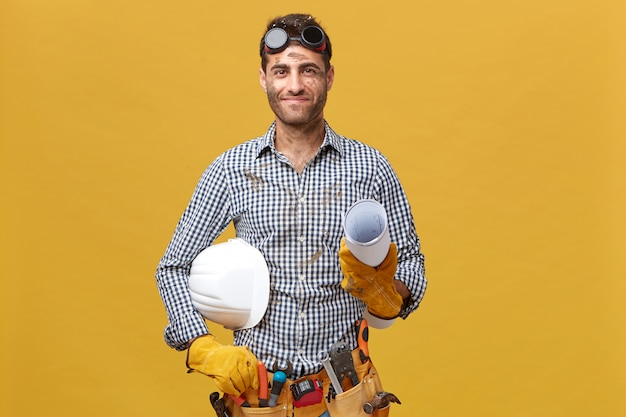 Pleased dirty man worker having protective goggles on head and holding rolled paper with hardhat isolated over yellow wall. professional handsome male with belt of tools going to work Free Photo