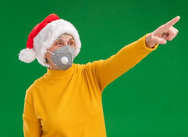 Lieta donna anziana con santa hat indossando maschera medica guardando e indicando il lato isolato su sfondo verde con copia spazio Foto Gratuite
