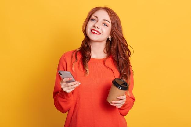 Довольная европейская женщина, одетая в повседневный оранжевый свитер, позирует, улыбается в камеру Бесплатные Фотографии