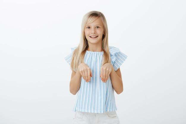 Довольная взволнованная маленькая девочка со светлыми волосами в модной синей блузке, держащая ладони на груди, как будто это кроличьи лапы, широко улыбаясь и удивленная, играя с остальными детьми на детской площадке Бесплатные Фотографии