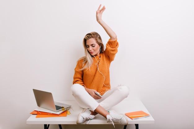 Довольная светловолосая женщина в модной спортивной обуви слушает музыку в наушниках и смотрит на экран ноутбука Бесплатные Фотографии