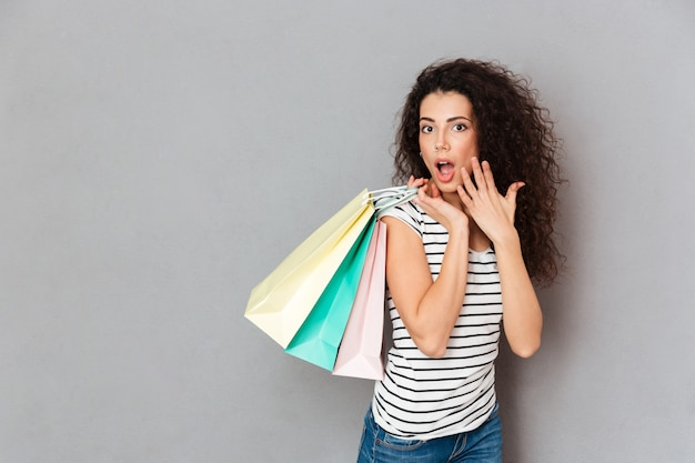 Pleased female shopaholic being excited with all purchases and packs spending day off in shopping mall Free Photo