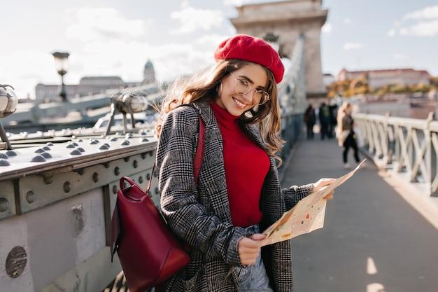Довольная женщина-путешественница в элегантном наряде проводит отпуск во франции Бесплатные Фотографии