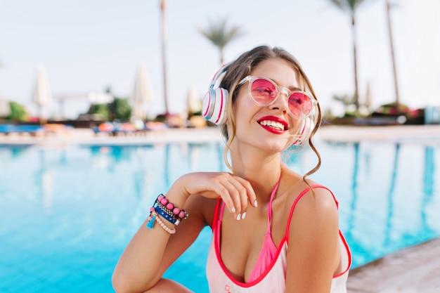 Довольная девушка с ярким макияжем и красочными аксессуарами наслаждается южным пейзажем под музыку Бесплатные Фотографии
