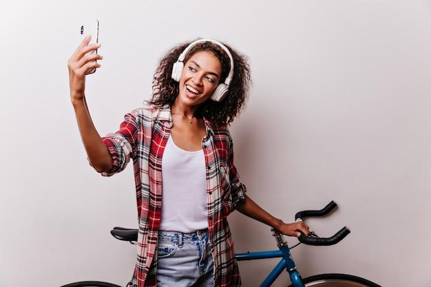 Ragazza soddisfatta con l'acconciatura riccia che fa selfie con la bicicletta. tiro al coperto di elegante donna africana che gode della musica su bianco Foto Gratuite