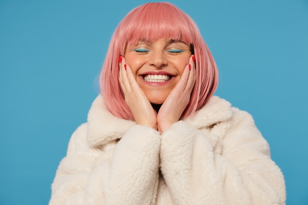Pleased good looking young cheerful pink haired woman holding her face with raised palms while standing, smiling happily with closed eyes, dressed in fancy clothes Free Photo