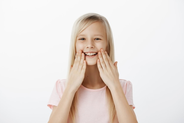 Pleased grinning adorable child with blond hair, smiling broadly and holding palms near lips, being amazed and satisfied with healthy teeth, attending dentist and feeling happiness Free Photo