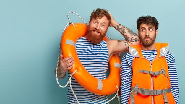 구명 조끼와 구명 부표와 함께 해변에서 포즈를 취하는 기쁘게 남자 무료 사진