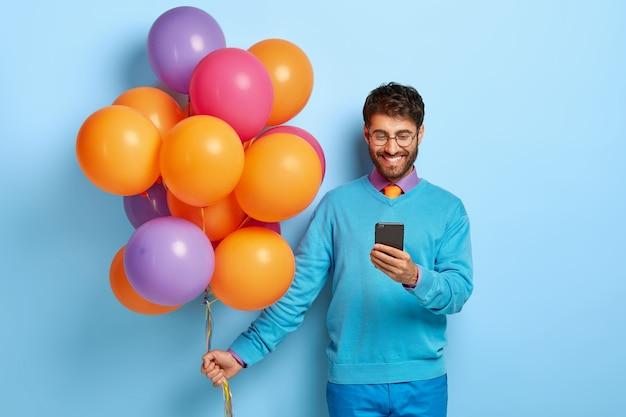 Felice l'uomo felice riceve un messaggio di congratulazioni sul cellulare, celebra la fine dell'università Foto Gratuite