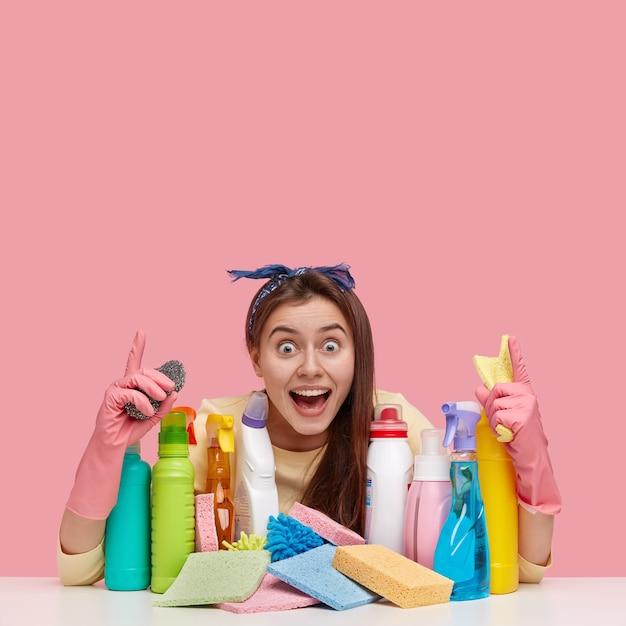 La donna felice e felice ha un'espressione felicissima, indica con entrambi gli indici il celiling Foto Gratuite