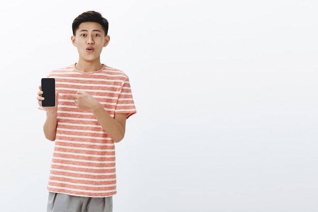 Pleased happy young cute asian guy in striped t-shirt standing to left side of copy space holding smartphone pointing at cellphone screen as showing awesome new phone to friends delighted Free Photo