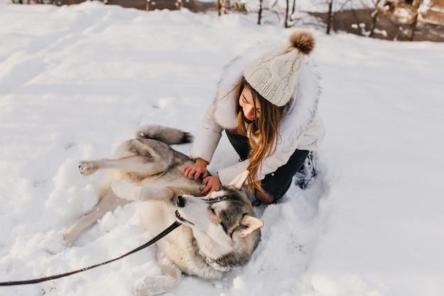 雪の上で休んでいる幸せなハスキーは、屋外で楽しみながら冬を楽しんでいます。 2月の寒い日に白い服なでる犬のスタイリッシュな若い女性の肖像画。 無料写真