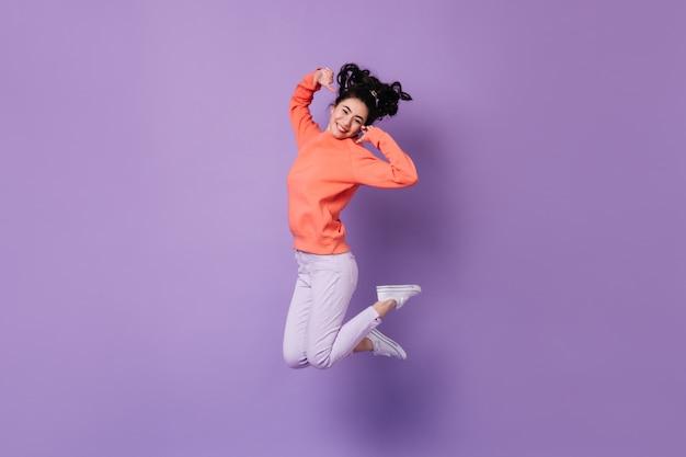 보라색 배경에 점프 기쁘게 일본 여자. 행복 한 아시아 젊은 여자의 스튜디오 샷입니다. 무료 사진