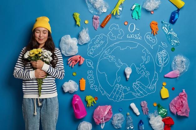 花束を手に入れて満足している韓国の女性は、白と黄色の花を持って、青い壁に描かれた惑星とプラスチックのゴミに立ち向かい、汚染から自然をきれいにします。 無料写真