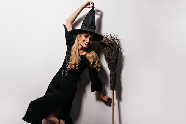 Приятная длинноволосая ведьма танцует с метлой. очаровательная женщина-волшебник, весело проводящая время на хэллоуин. Бесплатные Фотографии