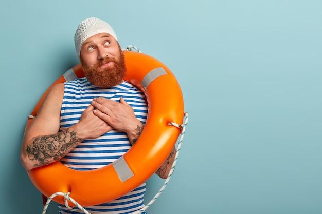 喜んでいる男性の水泳選手は感謝のしぐさをし、プロのレッスンと安全を保つためにライフグラッドまたは水泳インストラクターに感謝を感じます 無料写真