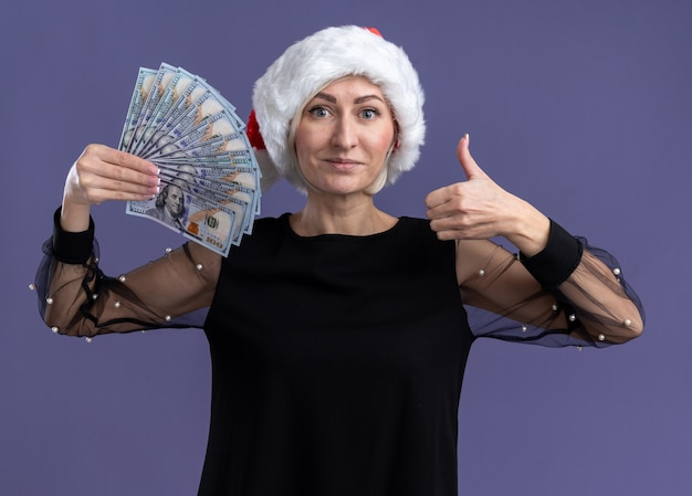 Pleased middle-aged blonde woman wearing christmas hat holding money looking at camera showing thumb up isolated on purple background Free Photo