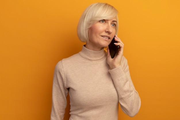 孤立した側を見て電話で話す幸せなかなり金髪のスラブ女性 無料写真